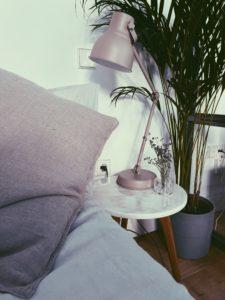 colchon con mesia, lampara y planta