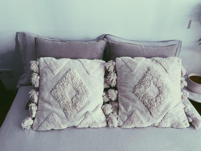 almohadas y cojines en una cama