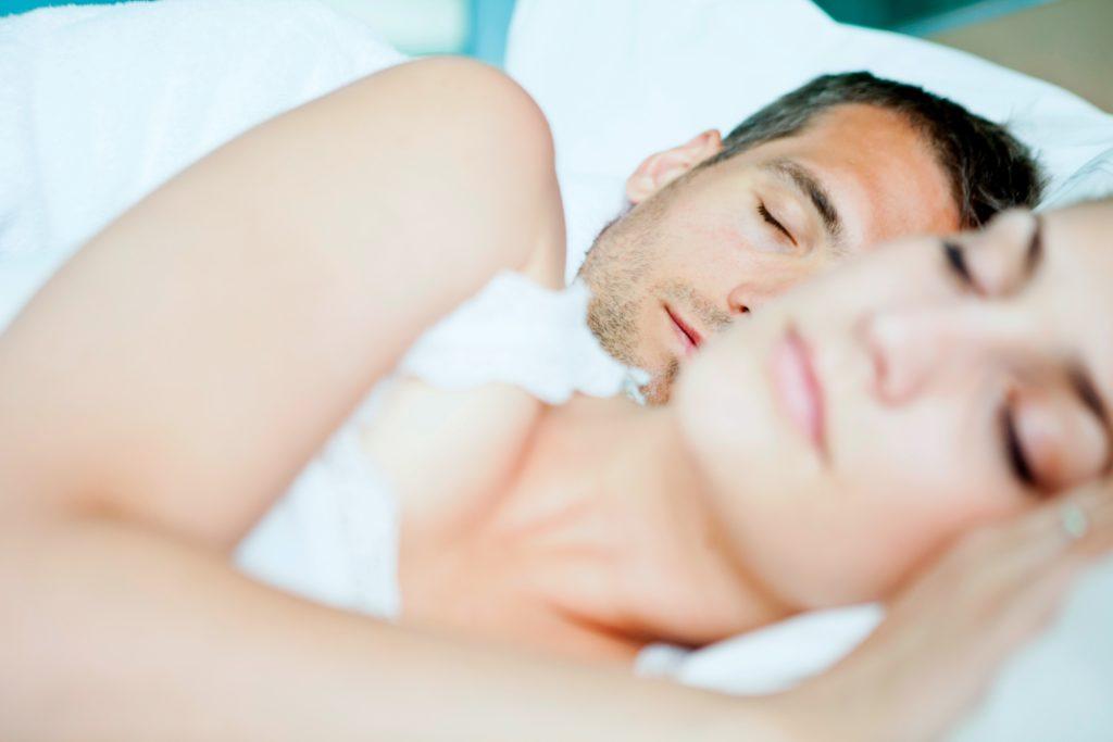 una pareja duermiendo en la cama