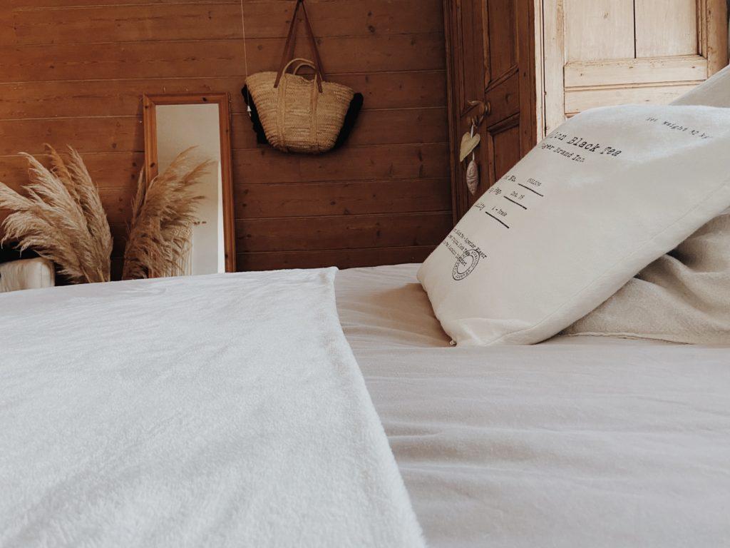 Cama con sabanas blancas y cojín en habitacion rustica