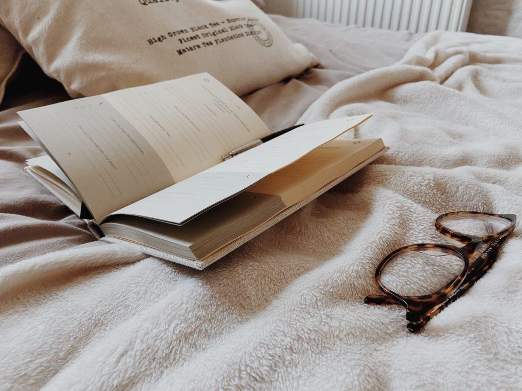cama con libro y gafas